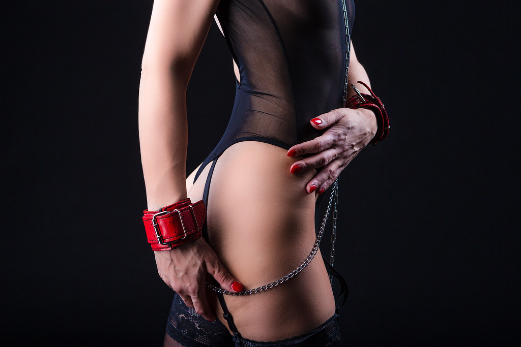 BDSM Concepts. Side View of Mature Caucasian Female Posing with  Accessories for Sado-Masochism Play. Tied with Chain and Wristbands. Against Black.