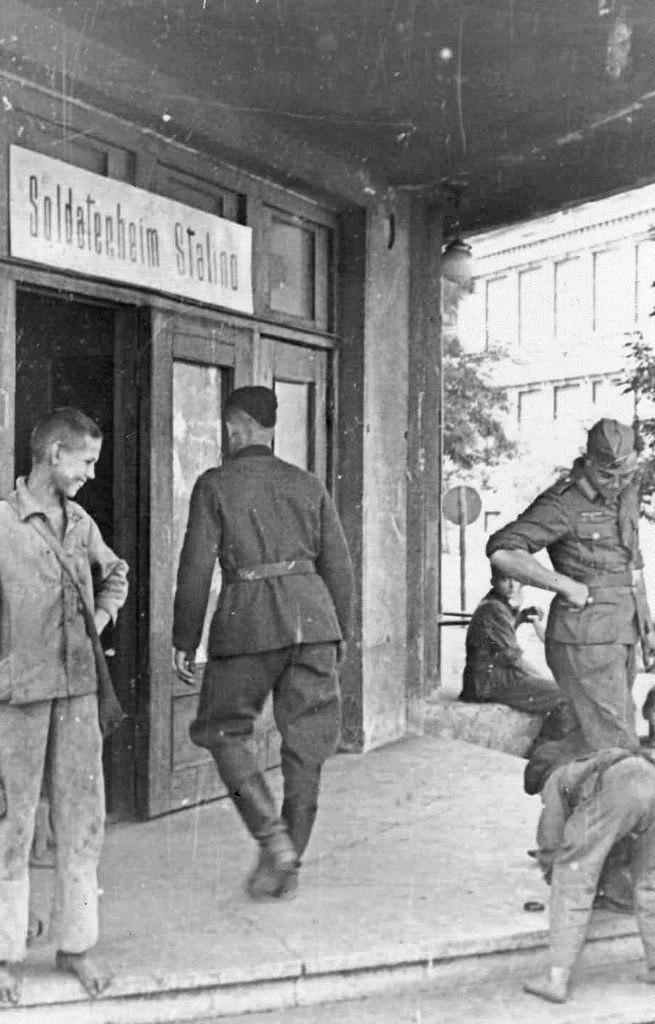 1942. Подросток чистит сапоги немецкому солдату у входа в гастроном «Москва» (во время оккупации — солдатский клуб) в оккупированном Сталино