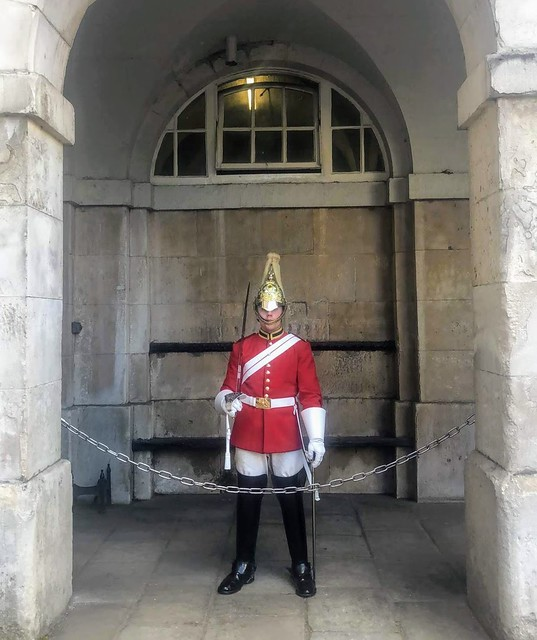 A London guard standing underneath a domed archway and behind a small chain.