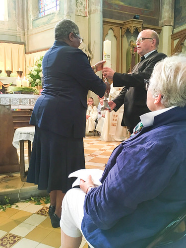 Winifred Ojo SSL handing over the devolution candle to the De La Salle Provincial, Frère Jean René Gentric, as a symbol of the Devolution of Trusteeship