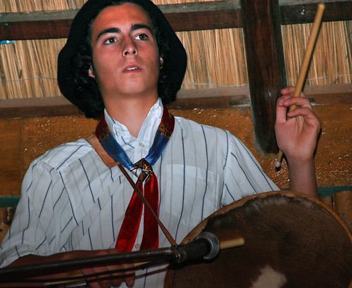 A drummer playing a cowskin drum on a 'estancia' (ranch) in the Argentinean countryside