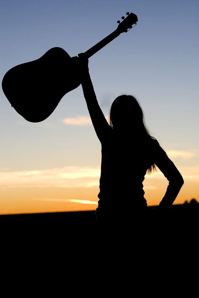 photo of woman triumphantly raising a guitar overhead