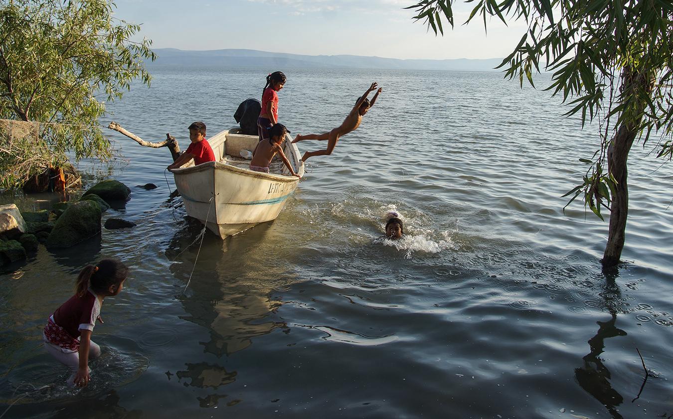 Pequeños de Agua Caliente juegan en la orilla del Lago