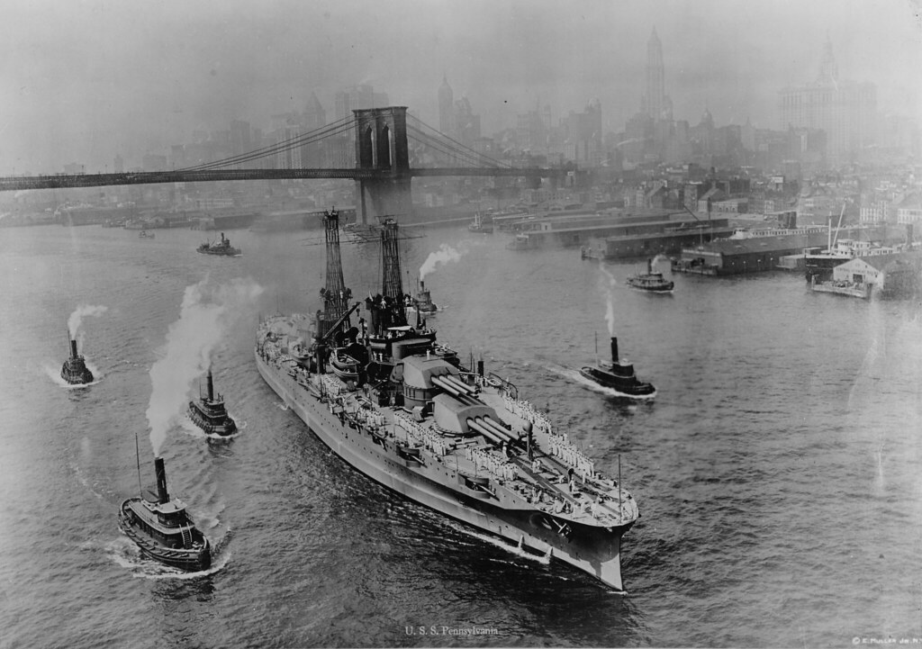 USS PENNSYLVANIA (BB-38) in the East River, New York City. Bound for the Brooklyn Navy Yard, 1916. New York City skyline and Brooklyn Bridge. She is escorted by local tugs.