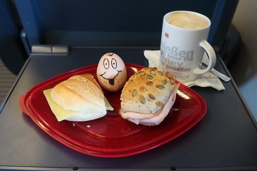 Für die Reise geschmierte Brötchen sowie gekochtes Ei zum am Platz servierten Milchkaffee aus dem Bordrestaurant des IC