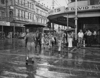 People crossing George Street in the rain, Brisbane, 1952