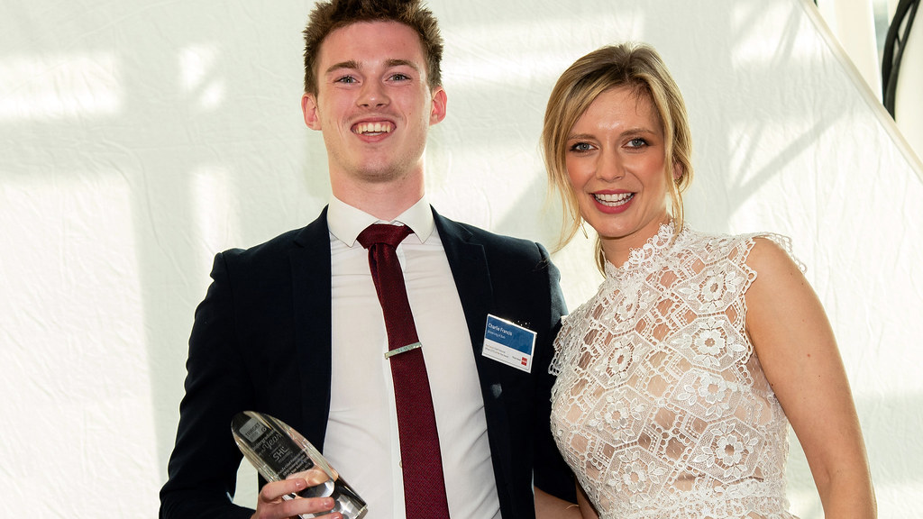 A smartly dressed smiling student holding his trophy with TV presenter Rachel Riley