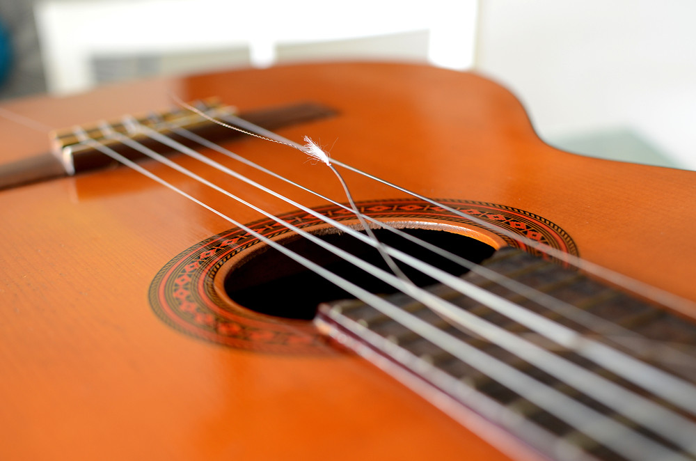 photo of classical guitar with broken string