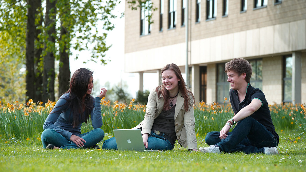 Maths students sitting outside on the grass on campus