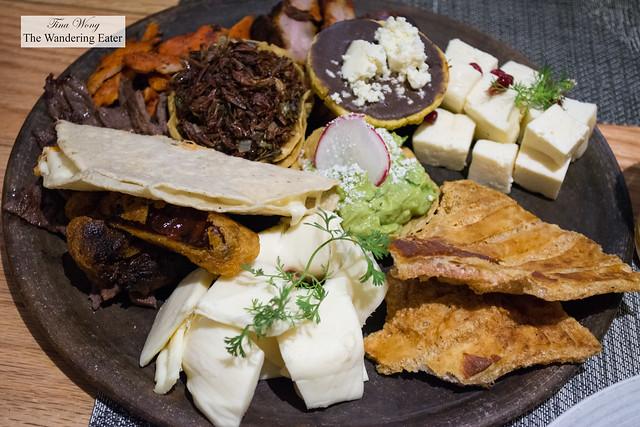 Oaxacan food sampler - Oaxacan cheeses, chicharrón, tostada with black bean puree, fried crickets, pork ribs, skirt steak, chicken