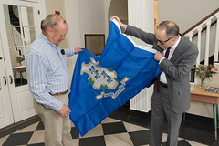 Washington First Selectman Mark Lyon and State Rep. Arthur O'Neill unfurl a new state flag provided to the town by Rep. O'Neill.