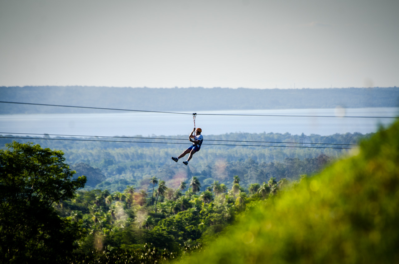 Un turista contempla el lago Ypacaraí desde las alturas del bosque ecológico El Escondido, durante un paseo en tirolesa que mide aproximadamente 600 metros y toma cerca de 2 minutos llegar de un extremo a otro. (Elton Núñez).