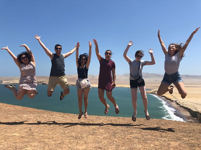 Five students jumping in the air near the shoreline in Ica, Peru.