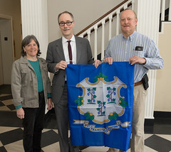 Washington Town Clerk Sheila Anson, State Rep. Arthur O'Neill and Washington First Selectman Mark Lyon pose with a new state flag provided to the town by Rep. O'Neill.