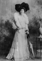 Woman wearing a large feathered hat and boa, posing for a portrait, 1900-1910