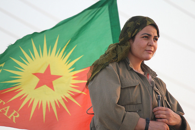 Kurdish fighter with PKK flag; taking down the patriarchy is crucial for the party to end the war - Créditos: Kurdishstruggle/Flickr/Creative Commons