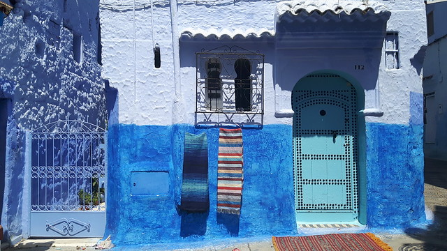 blue door with coloured rugs, Chefchaouen, Morocco