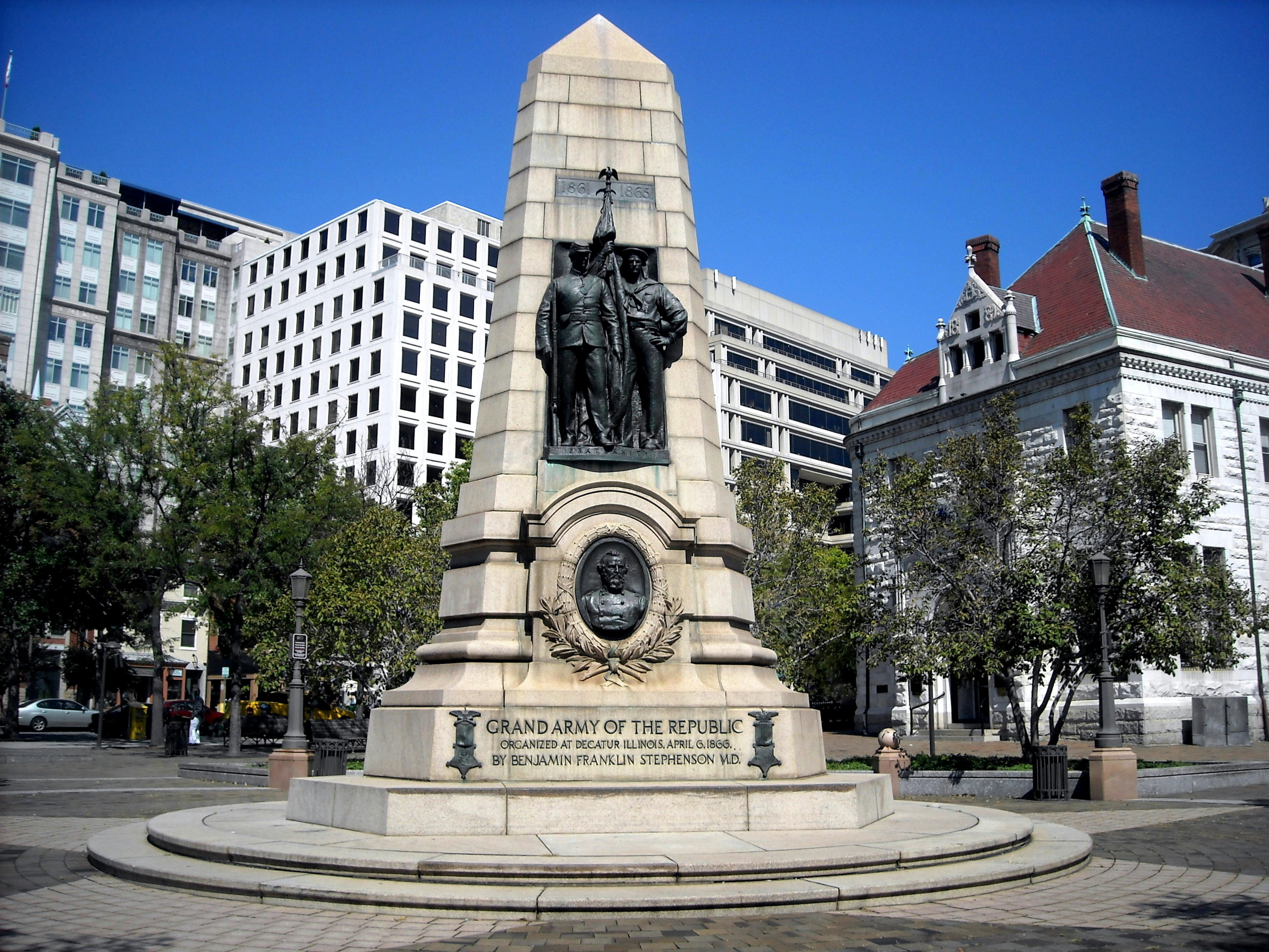 The Grand Army of the Republic Memorial (G.A.R. Memorial), also known as the Dr. Benjamin F. Stephenson Memorial, located at the intersection of 7th Street, C Street, and Pennsylvania Avenue, N.W., in the Penn Quarter neighborhood of Washington, D.C. The former National Bank of Washington is visible on the right-hand side. Sculpted by John Massey Rhind, and dedicated on July 3, 1909, the bronze sculpture honors Benjamin F. Stephenson, M.D., founder of the G.A.R. Photo taken on September 19, 2009.