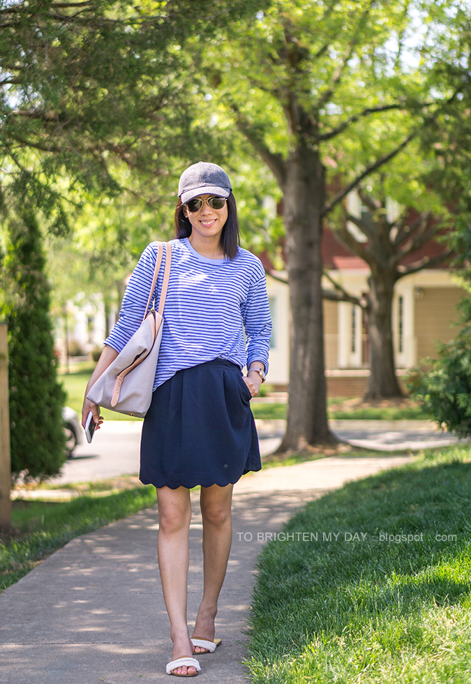 gray wool cap, blue striped top, oversized watch, navy scalloped skirt, beige and gray tote, white sandals with embellishments
