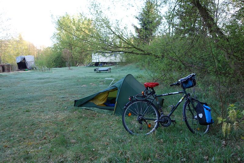 Das Zelt und das Fahrrad stehen im Schatten eines Hügels und allerlei Gestrüpp, auf einer taubedeckten Wiese. weiter hinten scheint schon die Sonne auf die Bäume.