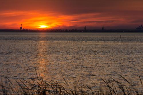 mobile bay alabama water dock docks sunset red glow clouds waves grass evening set sun sky