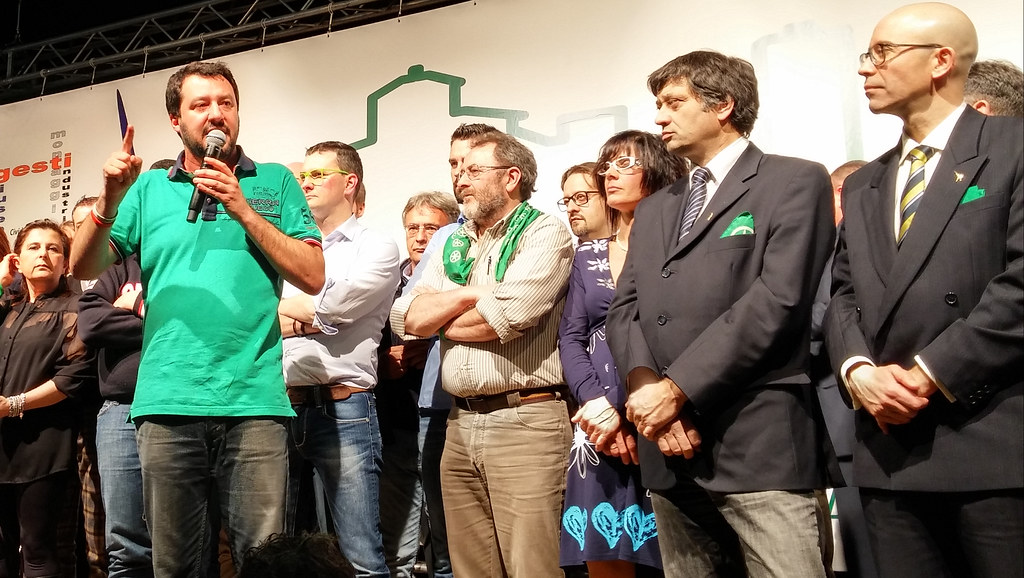 Matteo Salvini talking on stage surrounded by members of the Northern League