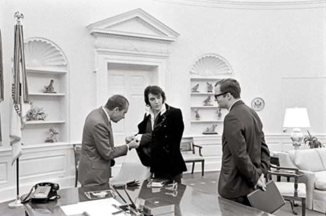 President Richard Nixon checks out Elvis Presley's cuff links during the latter's visit to the White House