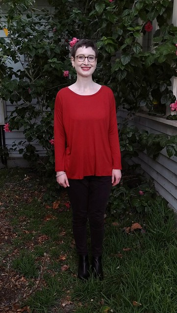 A woman stands in front of a hibiscus plant. She wears a drop shoulder, long sleeve red tee and black skinny pants.