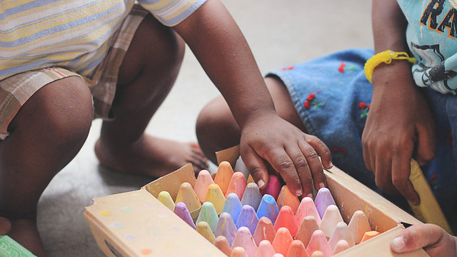 Children opening a box of coloured school chalk