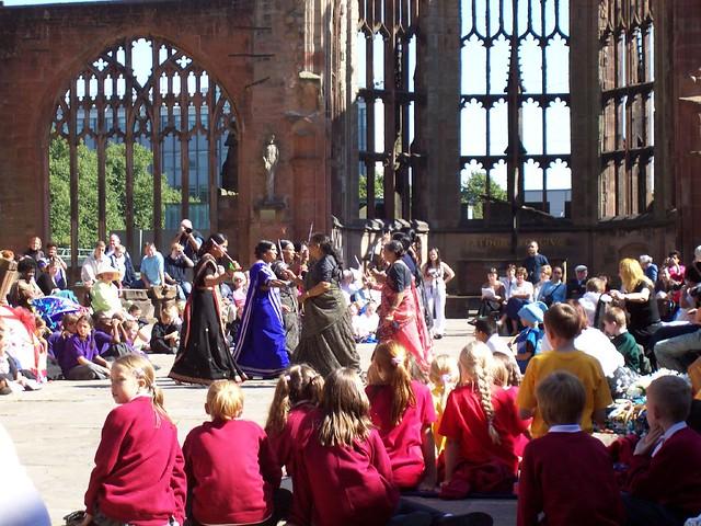 Dancing women with schoolchildren spectators