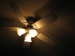 incandescent light bulb(1.0), light fixture(1.0), yellow(1.0), light(1.0), ceiling fan(1.0), ceiling(1.0), mechanical fan(1.0), circle(1.0), darkness(1.0), lighting(1.0),