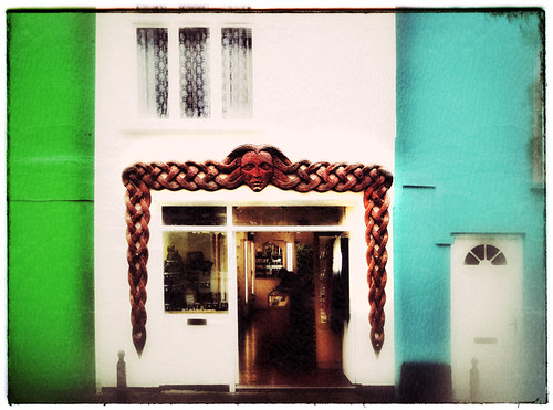 Carved wood of Celtic hair decorate a shop in Dingletown, Ireland, run through the photo app Snapseed