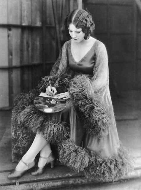 Joan Crawford modeling a cocktail dress trimmed with maribou feathers, 1925.  Photos by Ruth Harriet Louise