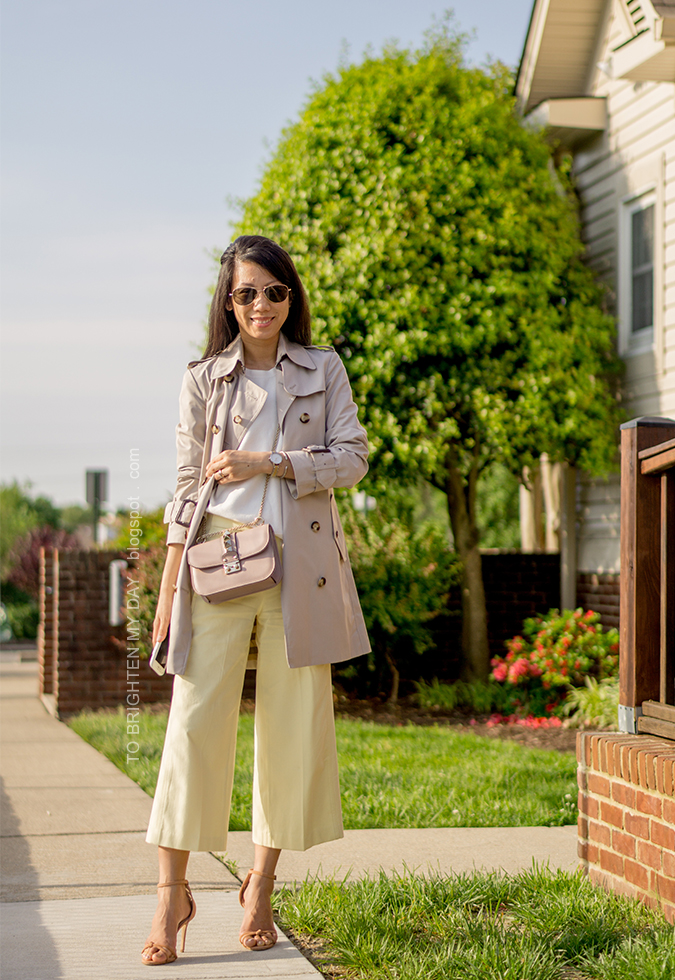trench coat, white sweater tee, nude crossbody bag, two tone watch, silver cuff, yellow wide leg cropped pants, brown knot sandals