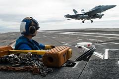 Aviation Boatswain's Mate Airman Alexander Dooley observes as an EA-18G Growler from Electronic Attack Squadron (VAQ) 141 lands aboard USS Ronald Reagan (CVN 76), May 30. (U.S. Navy/MCSN Tyra Watson)