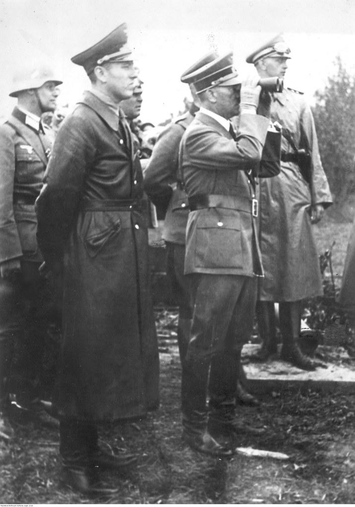 Адольф Гитлер, сопровождаемый солдатами, смотрит в бинокль на Гдыню. Рядом с ним в черном пальто Альберт Форстер