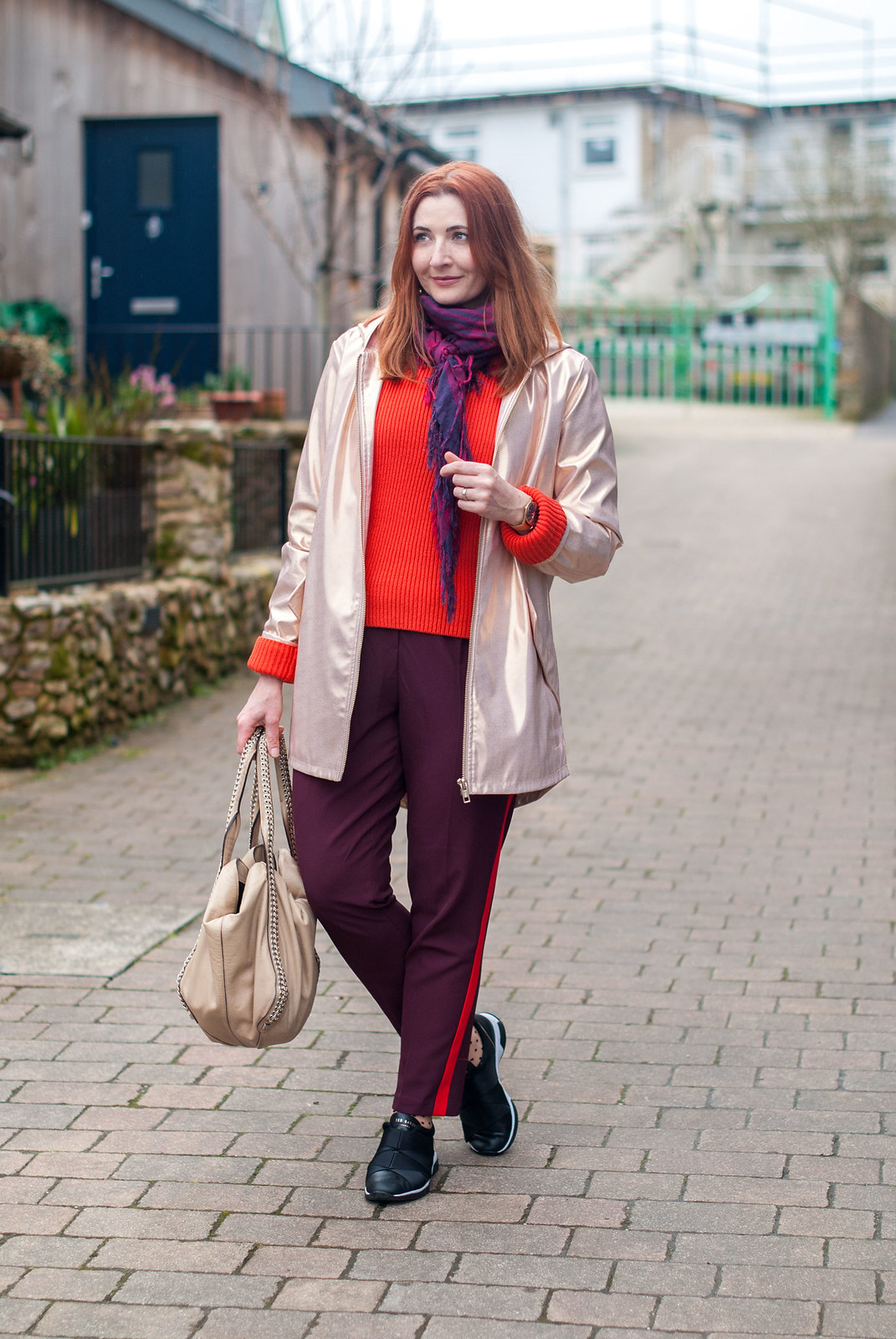 Beating April Showers in Metallics and Warm Colours \ rose gold raincoat \ orange-red sweater \ burgundy and red stripe trousers pants \ Ted Baker Queane trainers sneakers \ polka dot socks | Not Dressed As Lamb, over 40 style