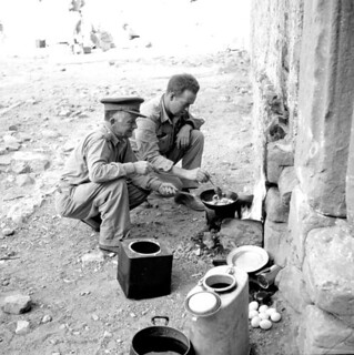 War correspondents Greg Clark (Toronto Star) and Ralph Allen (The Globe and Mail) cook... breakfast... / Les correspondants de guerre Greg Clark (Toronto Star) et Ralph Allen (The Globe and Mail) préparant le déjeuner...