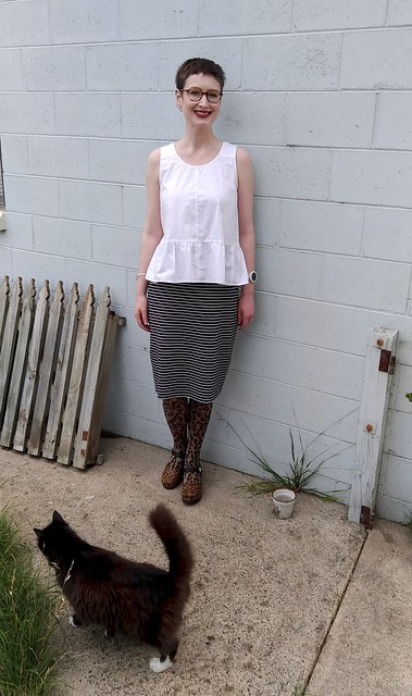 A woman stands in front of a blue brick wall. She wears a white peplum top, navy white stripe knit pencil skirt, and animal print tights and clogs. A cat passes by.