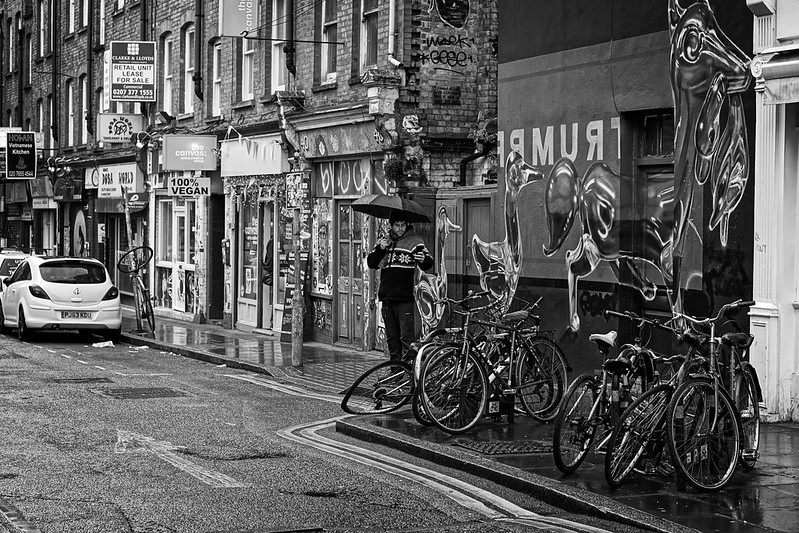 A man takes a photo of some bikes, near London's Brick Lane