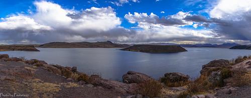 travel peru andes altiplano lake umayo sillustani landscape water rock grass sky cloud mountains