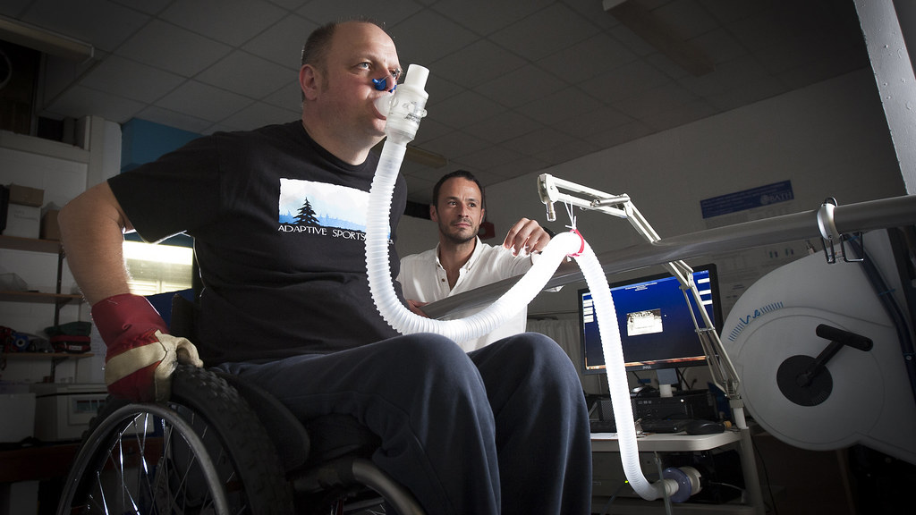 Researcher doing research on health and fitness of wheelchair users using a specially designed treadmill.