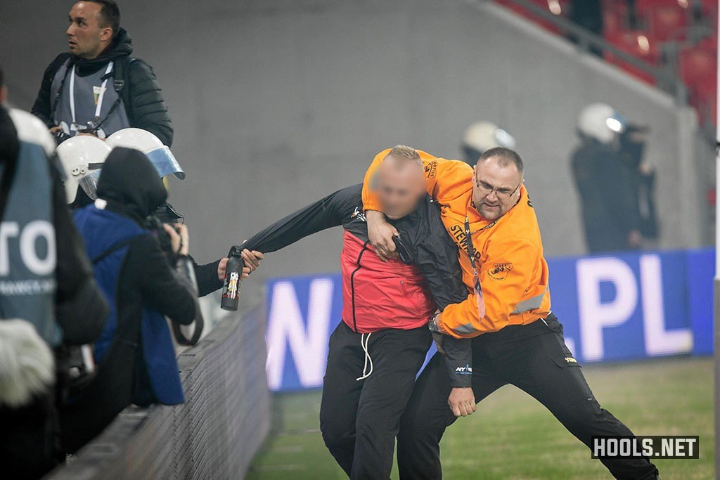 A GKS Tychy fan is tackled by a steward during the game against Ruch Chorzów.