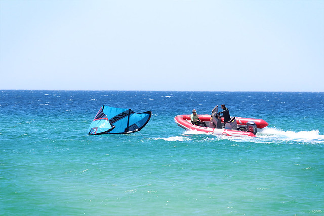 A man being picked up by a red speedboat dragging a kitesurfing kite.