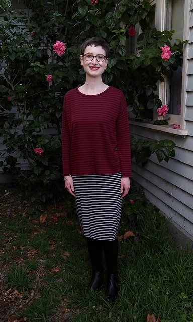 A woman stands in front of a hibiscus plant. She wears a burgundy drop shoulder, long sleeve knit tee with blue white stripe skirt.