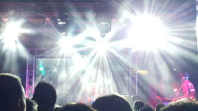 lights forming a starburst at a concert over a stage. The band can be seen behind the lights and concert attendees as silhouettes in the foreground
