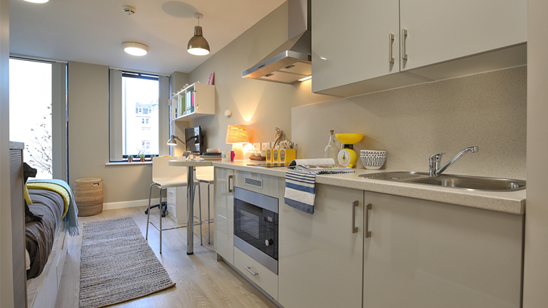 A kitchen in a studio bedroom