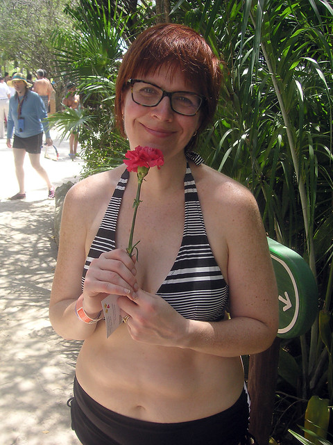 Me in my bikini holding a red carnation