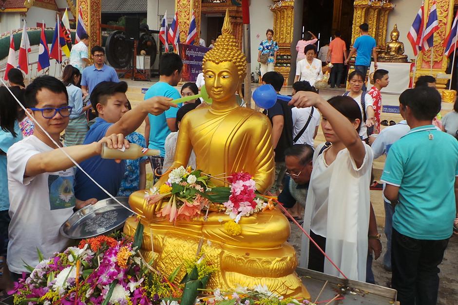 Umat Buddha menyiramkan air ke rupaka Buddha di Vihara Suan Tan, Provinsi Nan