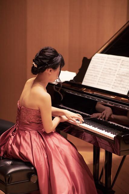 Beautiful woman playing piano in concert